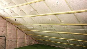 Underneath the roof sheathing and two exterior layers of rigid foam, the builder stapled netting to the underside of the rafters and filled the roof cavities of the unvented attic with thick R-38 blanket of blown-in fiberglass insulation.