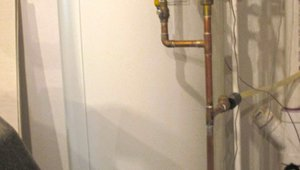 A centrally located 80-gallon storage tank holds hot water from the air-to-water heat pump.