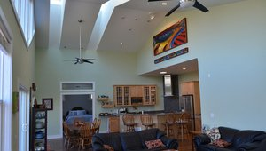 Tall ceilings and high-performance windows and skylights in the great room help flood the home's interior with natural daylight; the remote-controlled skylights and energy-saving ceiling fans provide ventilation and cooling when outdoor humidity is low.
