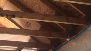 Raise heel trusses allow Garbett to get the full depth of insulation over the top plates to minimize cold spots along exterior walls. After installing baffles and ceiling drywall, the eaves areas will be air-sealed with spray foam, then the whole ceiling will be covered with R-60 of blown fiberglass.