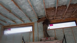 The vaulted living room ceiling had 7 inches of closed-cell spray foam plus an R-22 unfaced mineral wool batt for a total insulation value of R-68 while the remaining flat sections of ceiling had 22 inches of loose fill fiberglass blown over the ceiling deck for R-70 of insulation.