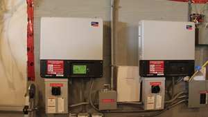 These inverters convert the direct current electricity produced by the solar electric system to alternating current. The house is wired with emergency circuits that tie into the inverters for power, refrigeration, and lighting during utility power outages.