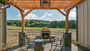 A sheltered patio provides a cool inviting outdoor retreat. The patio is surfaced with pavers to reduce the amount of impervious surfaces around the home.