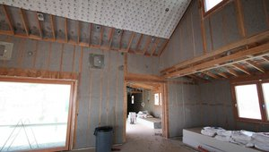 The 2-by-6 double-stud advance-framed walls are stuffed with R-56 of blown cellulose. Sheets of phase-change material are installed over the cellulose to help even out interior temperatures in this high-desert location.
