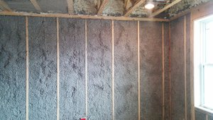 Blown cellulose is dense-packed to completely fill the spaces between and around the 2-by-4 studs, which are staggered on the 2-by-6 top and bottom plates. Alternating studs are hidden from view in this photo because they are set back to align with the outside edge of the 2-by-6 allowing the inside edge to be covered with insulation, which effectively stops heat transfer through the wall.