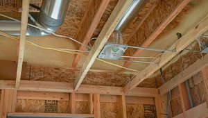 Spray foam insulation was applied to the rim joists to provide insulation and draft protection. Duct work runs through the space between the floor joists for efficient heating and cooling air distribution.