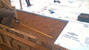Rigid foam insulation will extend under the full slab and over the top of the footing wall to completely isolate the slab from the ground and the footings.