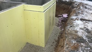 The concrete basement walls and floor are wrapped in a thermal blanket of R-10 rigid foam insulation.