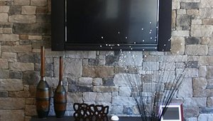 The traditional styling of the stone evokes the look of a family farm house as a backdrop to the family room wall, one of the home's main gathering places.
