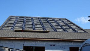 The photovoltaic panels sit in a heavy-duty plastic tray that was installed directly on the roofing underlayment. The roofing shingles are installed around but not under the tray so if they need to be replaced, the panels can stay in place.