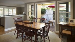 <p>The dining room and living room are the only rooms in the house that did not change location with the new layout. The half wall was once a full wall, and the doorway between the two rooms was knocked out to open up the spaces while still keeping some definition between them.</p>  <p>Aluminum-clad double doors in the dining room look out to the garden and open to the patio&rsquo;s comfortable sitting and reading area.</p>