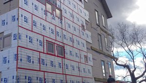 Exterior rigid foam insulation is taped at the seams to provide a continuous thermal blanket, comprehensive draft protection, and a continuous wall water barrier.